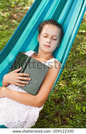 Romantic teenage girl lays on hammock with book of memories - stock photo