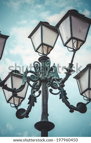 romantic, traditional street lamp with decorative metal flourishes - stock photo