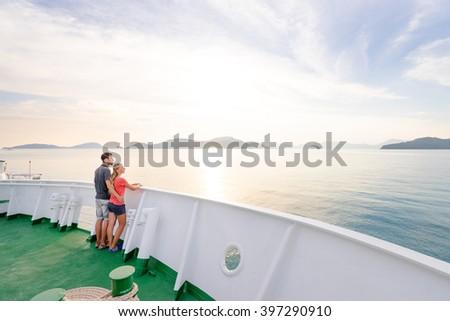Romantic vacation. Young loving couple enjoying sunset on cruise ship deck. Sailing the sea. - stock photo