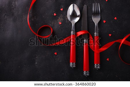 Romantic Valentine's Day celebration, a set of silverware on a dark background,decorated with red ribbon and hearts.selective focus - stock photo