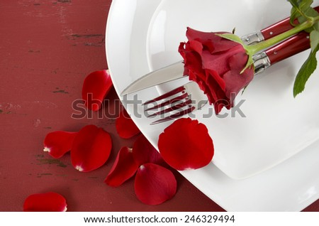Romantic Valentines Day table place setting with white heart shape plates with rose and petals on red wood background, overhead.