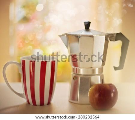 Romantic vintage style image of morning coffee with moka pot and striped mug. Bokeh effect, haze, color toning - stock photo