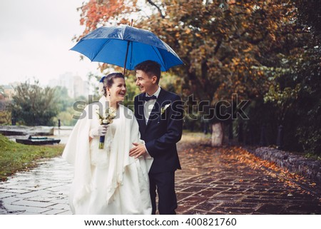 Romantic walking of newlyweds. The groom and bride are walking under umbrella in the park at their wedding day. Groom and bride looking each to other. Couple are smiling, they are happy. - stock photo