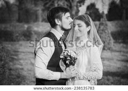 Romantic wedding couple embracing at each other with bouquet in hands
