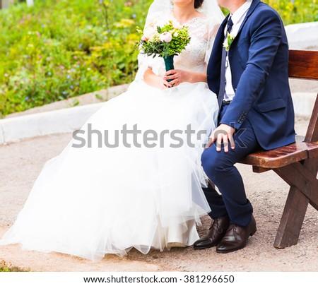 Romantic wedding couple with bridal bouquet sitting on a bench in the park
