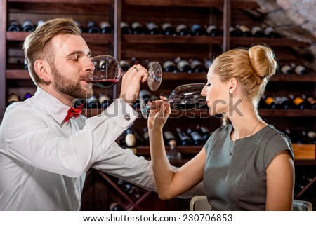 Romantic well-dressed couple drinking wine at the cellar