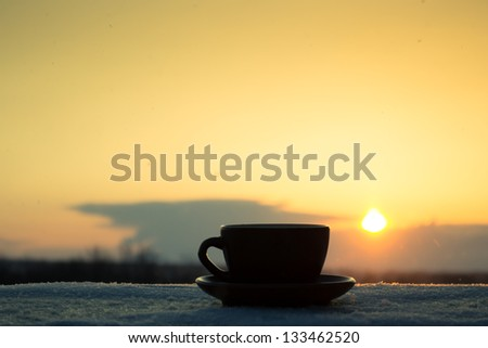 Romantic winter evening. Cup of coffee or tea in rays of sunset - stock photo