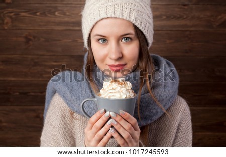 Romantic Winter Hipster Girl in Knitted Sweater and Beanie Hat Enjoying a Cup of Hot coffee in Hands. Lovely Dreaming Woman. Warming Up Concept.