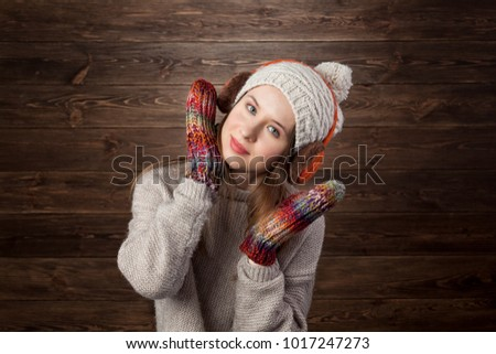 Romantic Winter Hipster Girl in Knitted Sweater and Beanie.Lovely Dreaming Woman. Wodden Wall Background. Warming Up Concept. Toned Photo with Copy Space.