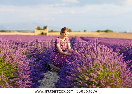 Romantic woman in lavender fields, having vacations in Provence, France. Girl traveling through Valensole plateau and making flower bouquet. - stock photo