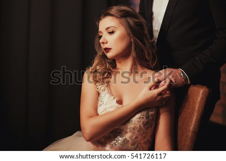 romantic Woman in pink bridal dress sitting on brown armchair. the bride holding the groom's hand. Indoor, interior, studio