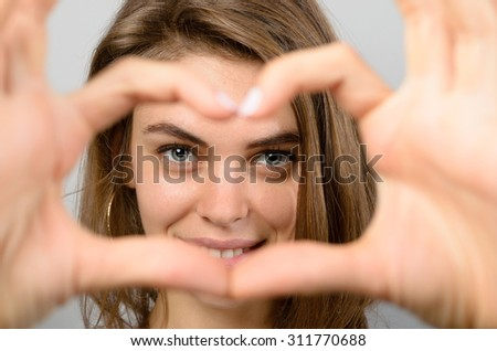 Romantic woman making a heart gesture with her hands framing her laughing eyes as she shows her feelings of love and affection - stock photo