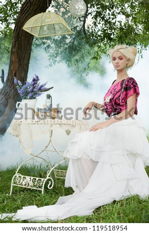 Romantic woman on a picnic in a fairy foggy forest. - stock photo