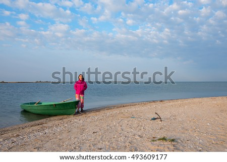 Romantic woman relaxes near small boat on the beach, looking on the sky and dreaming. Windy weather on the sea coast during sunrise.