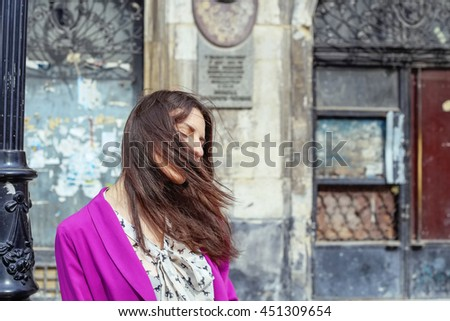 Romantic woman with windy hair with closed eyes dreaming on the old city street. Fashionable woman in bright pink jacket and chiffon blouse with a bow, street fashion look, summer outfit. - stock photo