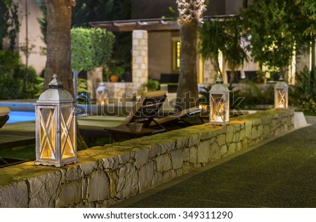 Romantic wooden lamps adorn the stone walls in the beach area ,on the street one of the resort towns of Crete island at night.District of Rethymno.Greece.Europe.