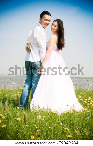 Romantic young asian couple in love in field of yellow flowers. - stock photo