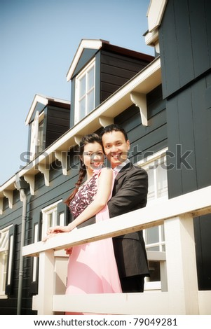 Romantic young asian couple in love on balcony of old dutch house.