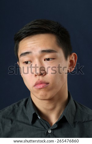 Romantic young Asian man looking down - stock photo