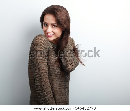 Romantic young beautiful woman holding hair in warm sweater on blue background
