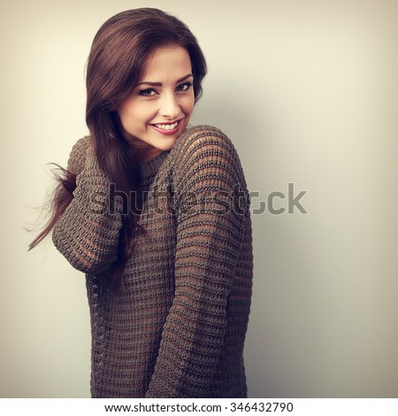 Romantic young beautiful woman holding hair in warm sweater. VIntage portrait