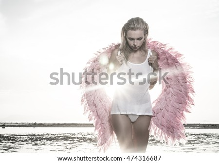Romantic young beauty as an angel on the beach in the morning. Blonde pretty female woman wearing pink wings, white t-shirt and bikini bottom looking down over sea and sky background