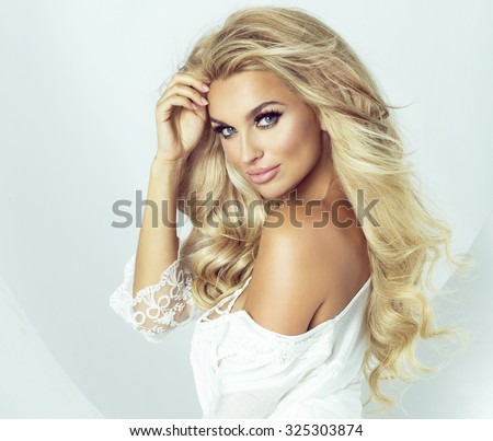 Romantic young blonde woman looking at camera. Fashion photo. Girl with long healthy hair and perfect makeup. Studio shot. - stock photo