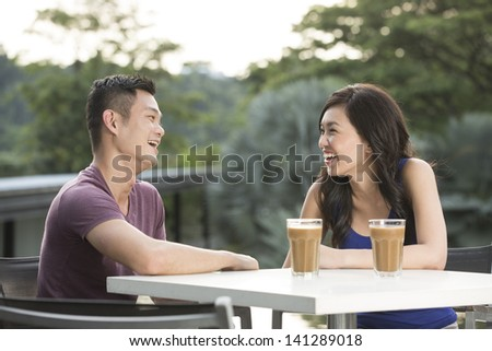 Romantic Young Chinese Couple Enjoying a Coffee out together.