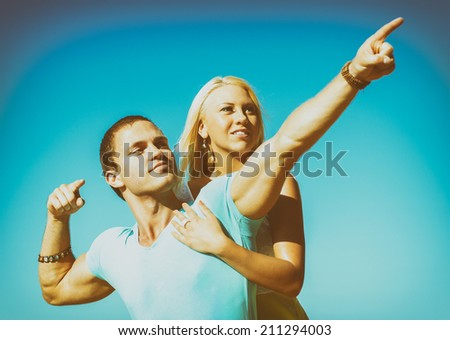 Romantic young couple against blue sky.