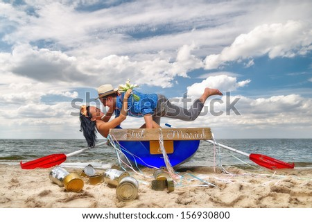 Romantic young couple cuddling in rowboat at lake - stock photo