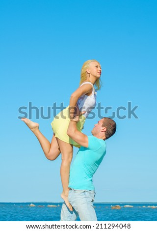 Romantic young couple dancing by the sea. - stock photo