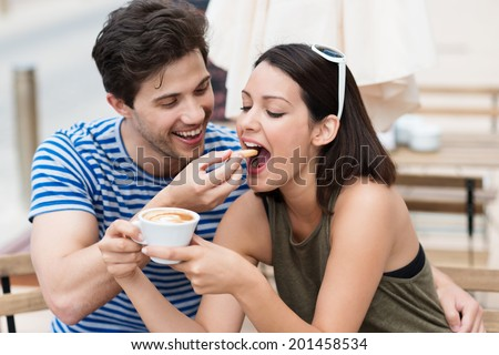 Romantic young couple drinking coffee with the young man laughingly feeding a biscuit to his girlfriend or wife as she holds a cup of cappuccino - stock photo