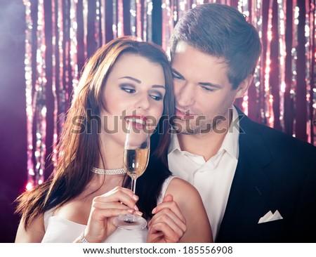 Romantic young couple enjoying champagne at nightclub - stock photo