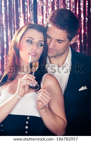 Romantic young couple enjoying champagne at nightclub