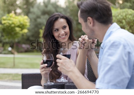 Romantic young couple having red wine in park - stock photo