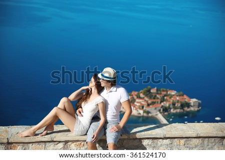 Romantic young couple in love over sea shore above Sveti Stefan island in Budva, Montenegro. Travel. Vacation. Family.  - stock photo