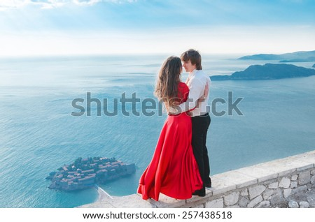 Romantic young couple in love over sea shore background. Fashion girl model in blowing red dress with handsome man in front of Sveti Stefan, Montenegro.  - stock photo