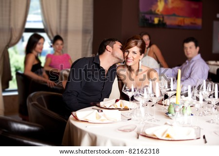 romantic young couple in restaurant date kiss - stock photo