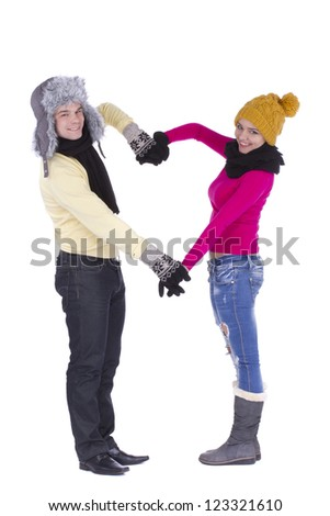 Romantic young couple in winter clothes making heart shape with arms on white