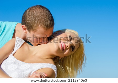Romantic young couple kissing against blue sky.