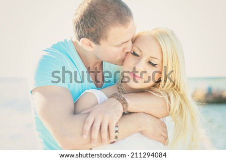 Romantic young couple kissing on the beach. - stock photo