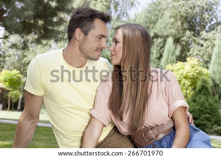 Romantic young couple looking at each other in park - stock photo