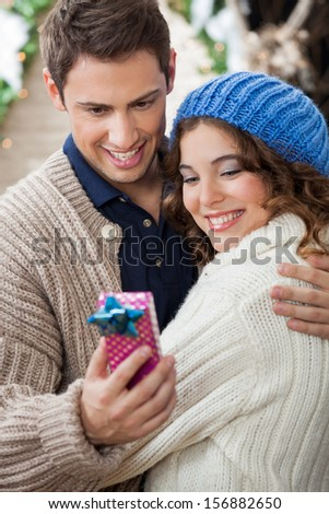 Romantic young couple looking at gift box while embracing at Christmas store - stock photo