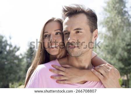 Romantic young couple looking away in park