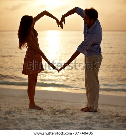 Romantic young couple making heart shape with arms on beach at sunset - stock photo