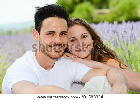 romantic young couple, man and woman during summer holiday having fun in lavender field in provence south France - stock photo