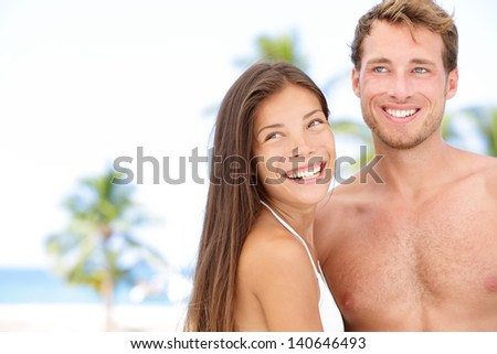 Romantic young couple on beach vacation smiling happy to the side. Newlywed young interracial couple on honeymoon enjoying summer sun on holidays travel in the tropics. Asian woman, Caucasian man.
