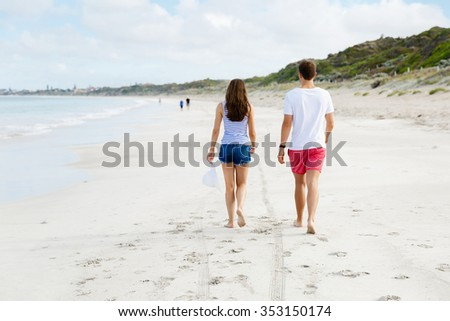 Romantic young couple on the beach waloking along the shore