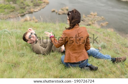 Romantic young couple relaxing on a grassy hill near a wide fast flowing river enjoying a tender moment alone together - stock photo