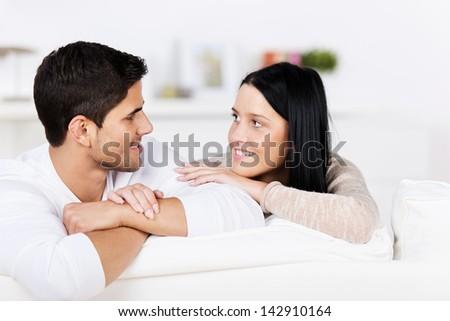 Romantic young couple relaxing on a sofa at home looking into each others eyes with tenderness and love - stock photo